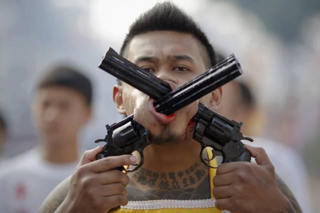 Ein Mann rammt sich zwei Pistolenläufe durch die Backen.